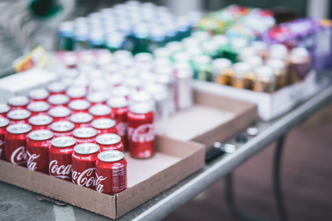 Selective Focus Photography of Red Coca-cola Can Lot on Box
