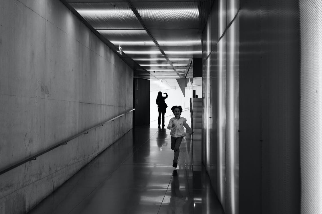 Person Running on Hallway Grayscale Photo