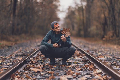 Man Holding Maple Leaf In The Middle Of Train Tracks During Day