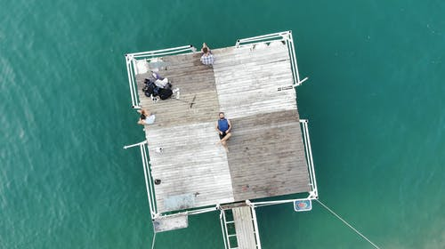Person Lying on Brown Wooden Platform on Body of Water
