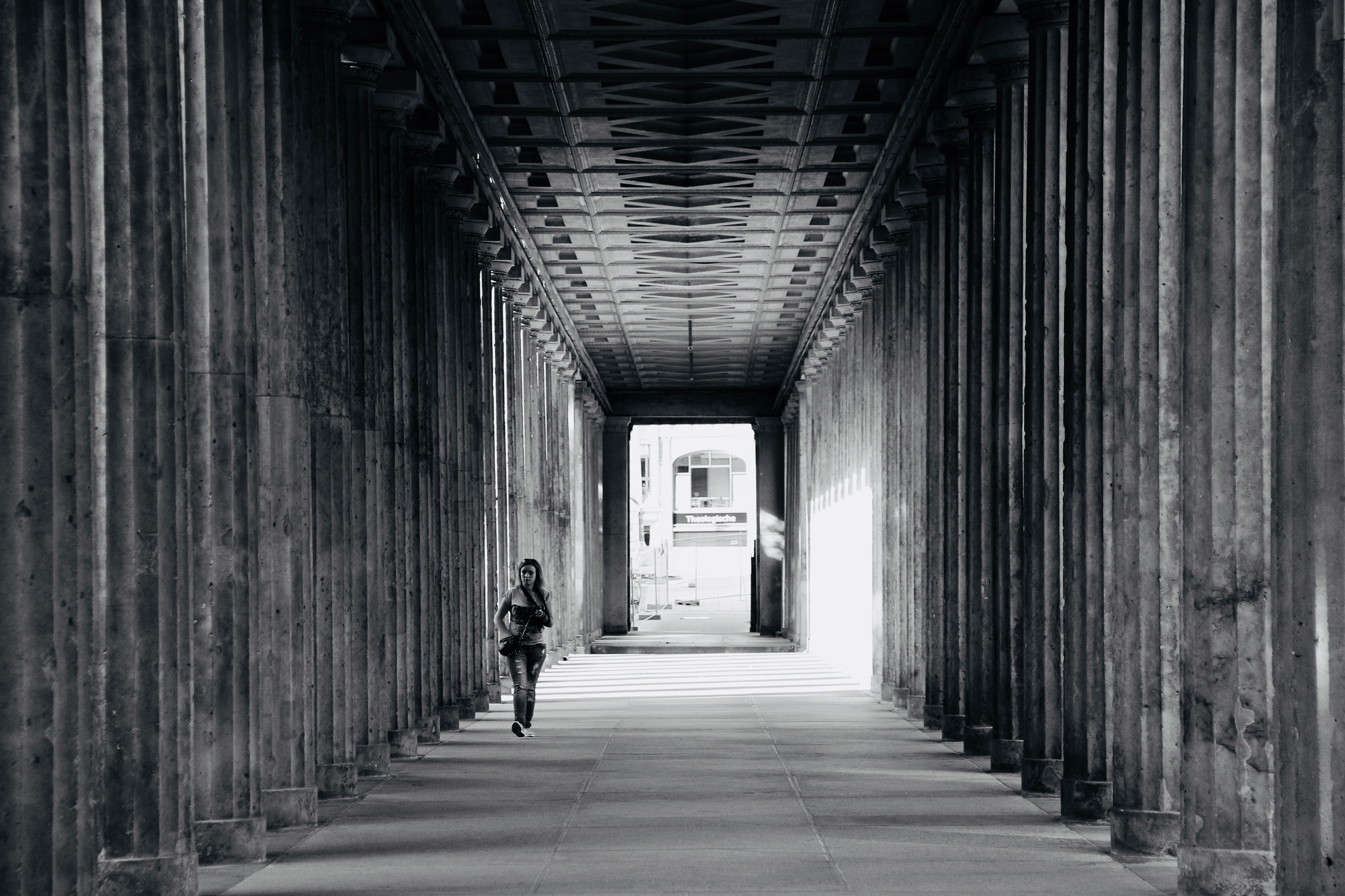 Grayscale Photo of Person Walking Near Columns
