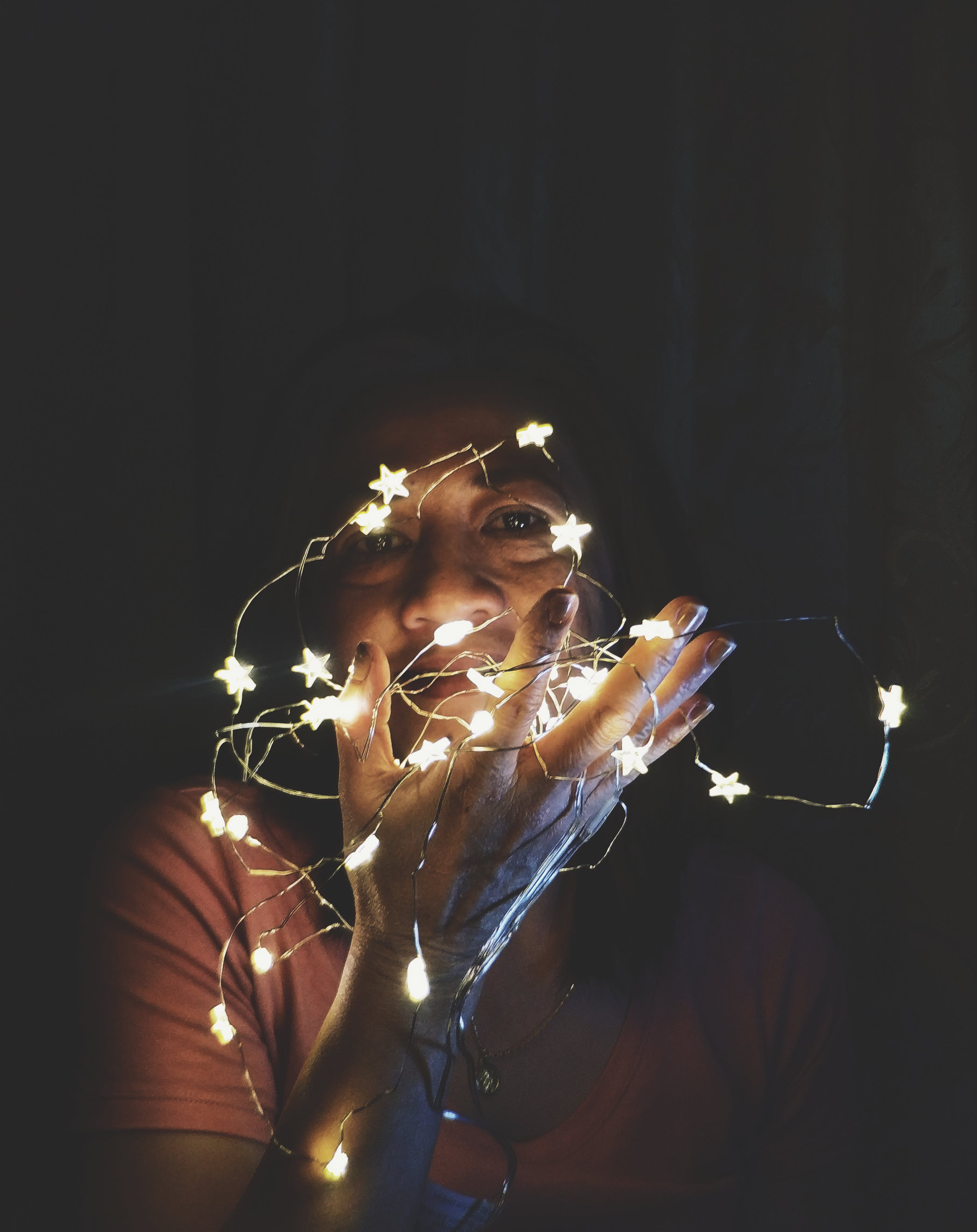 Close-Up Photo of a Woman Holding String Lights