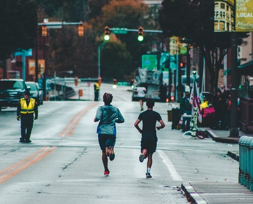 Two Men Running On Concrete Road