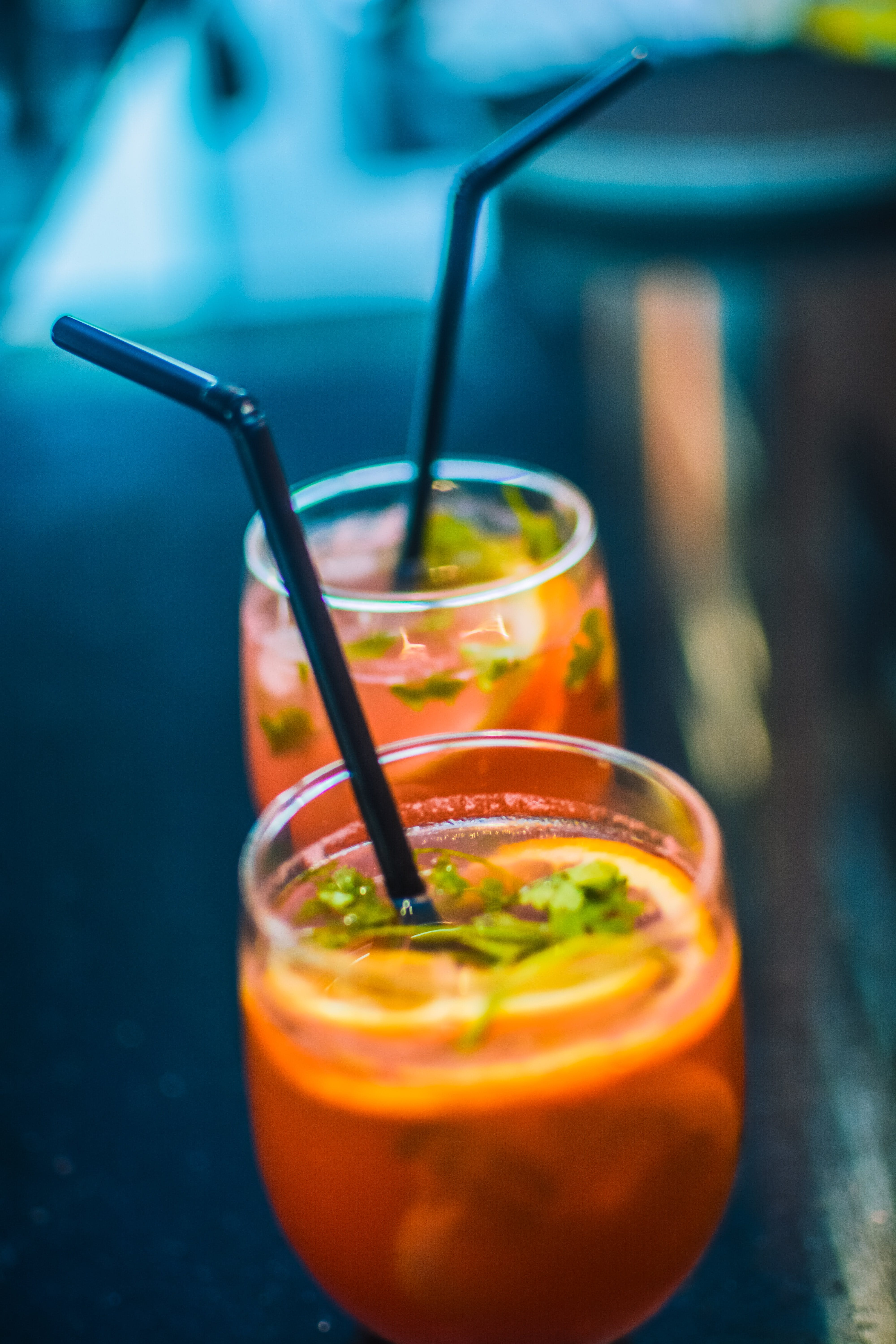 Two Beverages In Footed Glasses With Black Straws