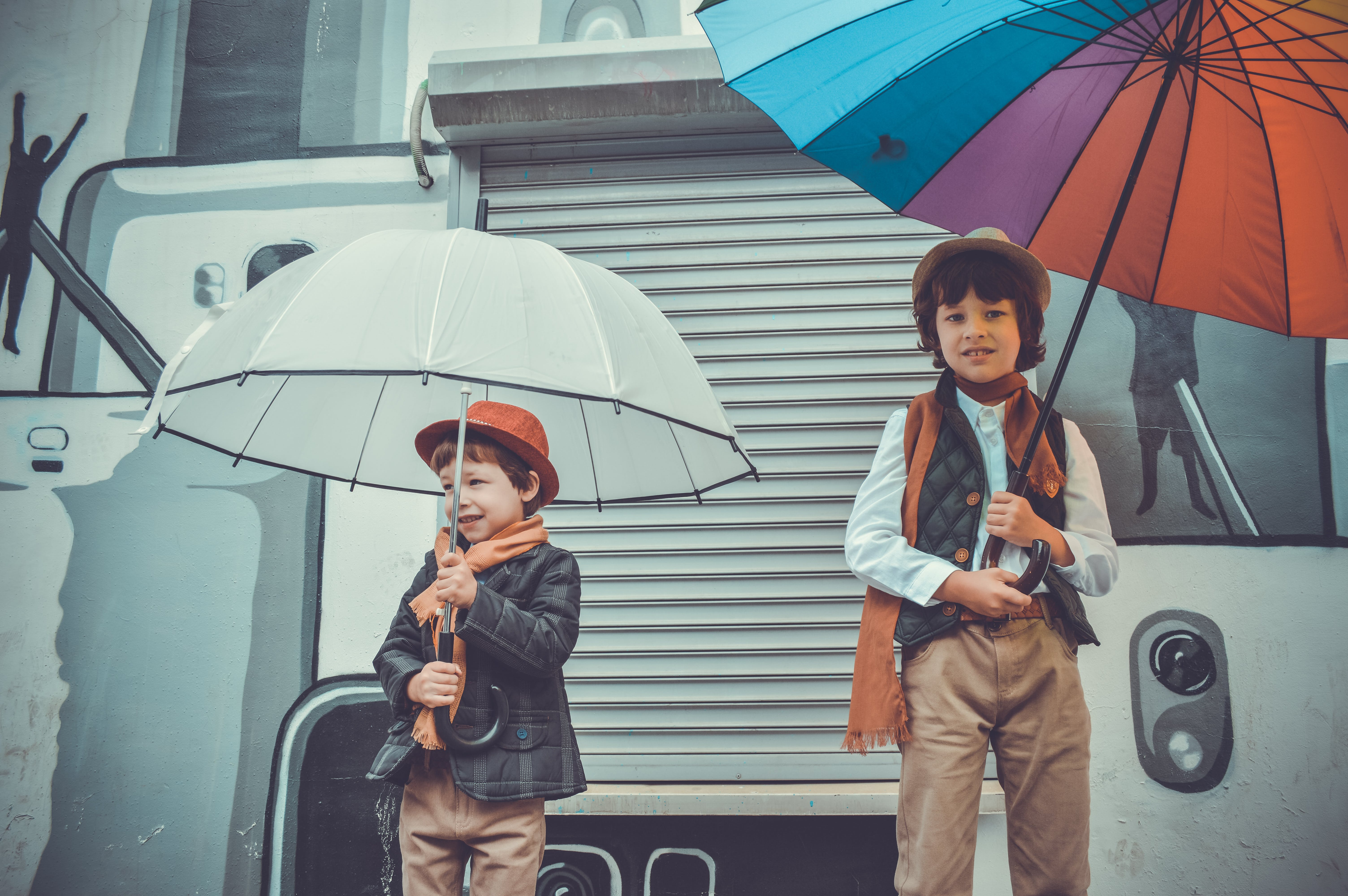 Two Children Holding Umbrellas While Smiling