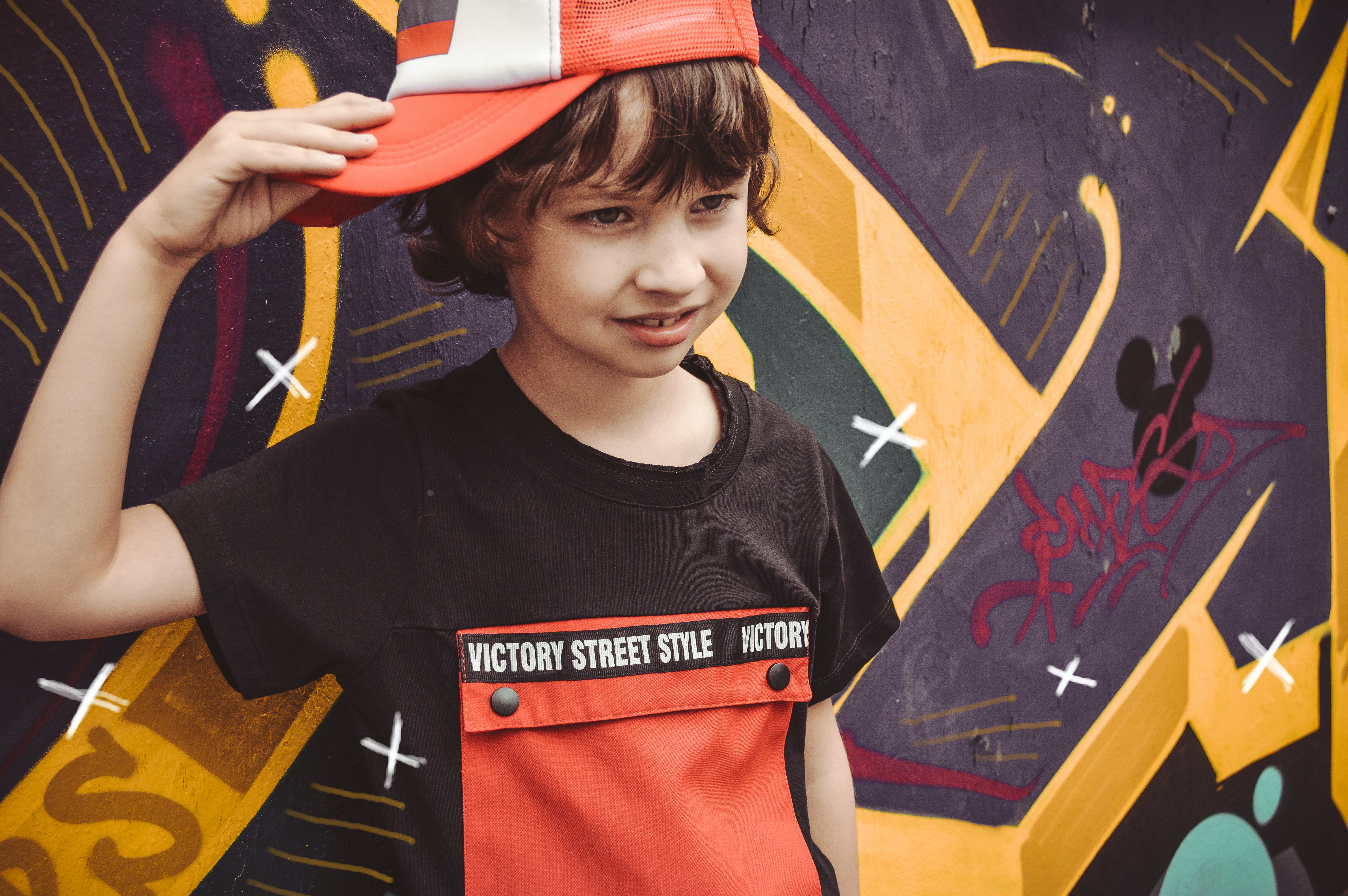 Boy Wearing Fitted Cap While Standing Beside Graffiti