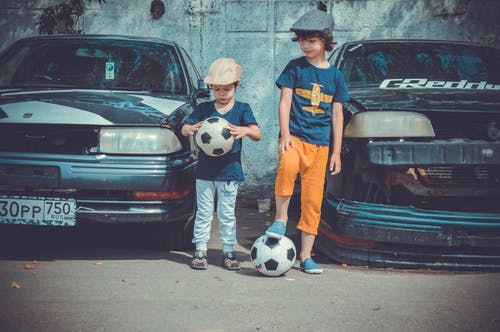 Two Boys Playing Soccer Ball Beside Cars