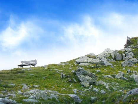 White Wooden Bench in Mountain during Daytime