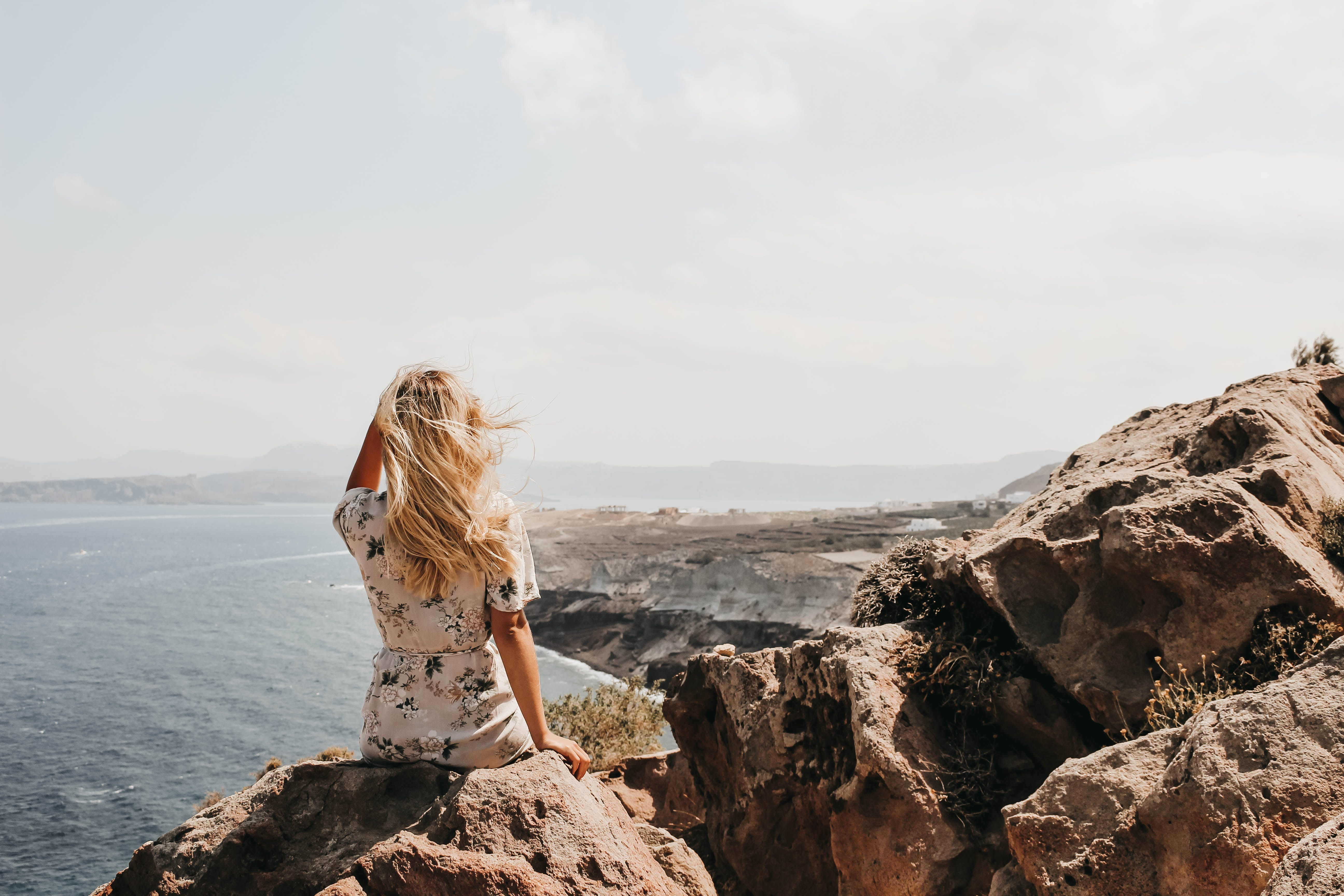 Woman Sitting on a Cliff Watching the Body of Water