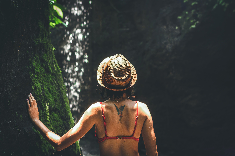 Woman in Bikini Top Wearing Hat Touching Tree