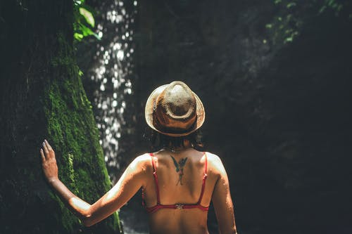 Woman in Bikini Top Wearing Hat Touching Tree