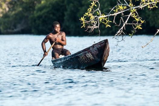 Man in Black Shorts Riding Rowboat during Daytime