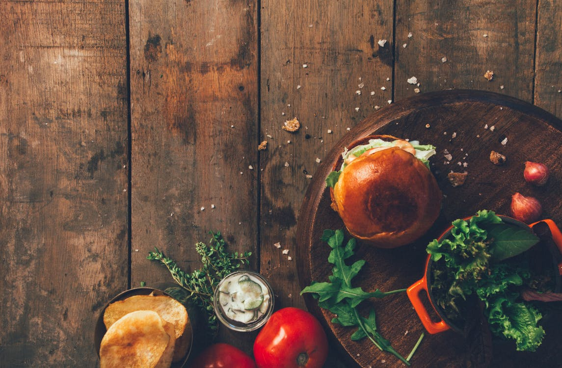 Burger and Vegetables Placed on Brown Wood Surface