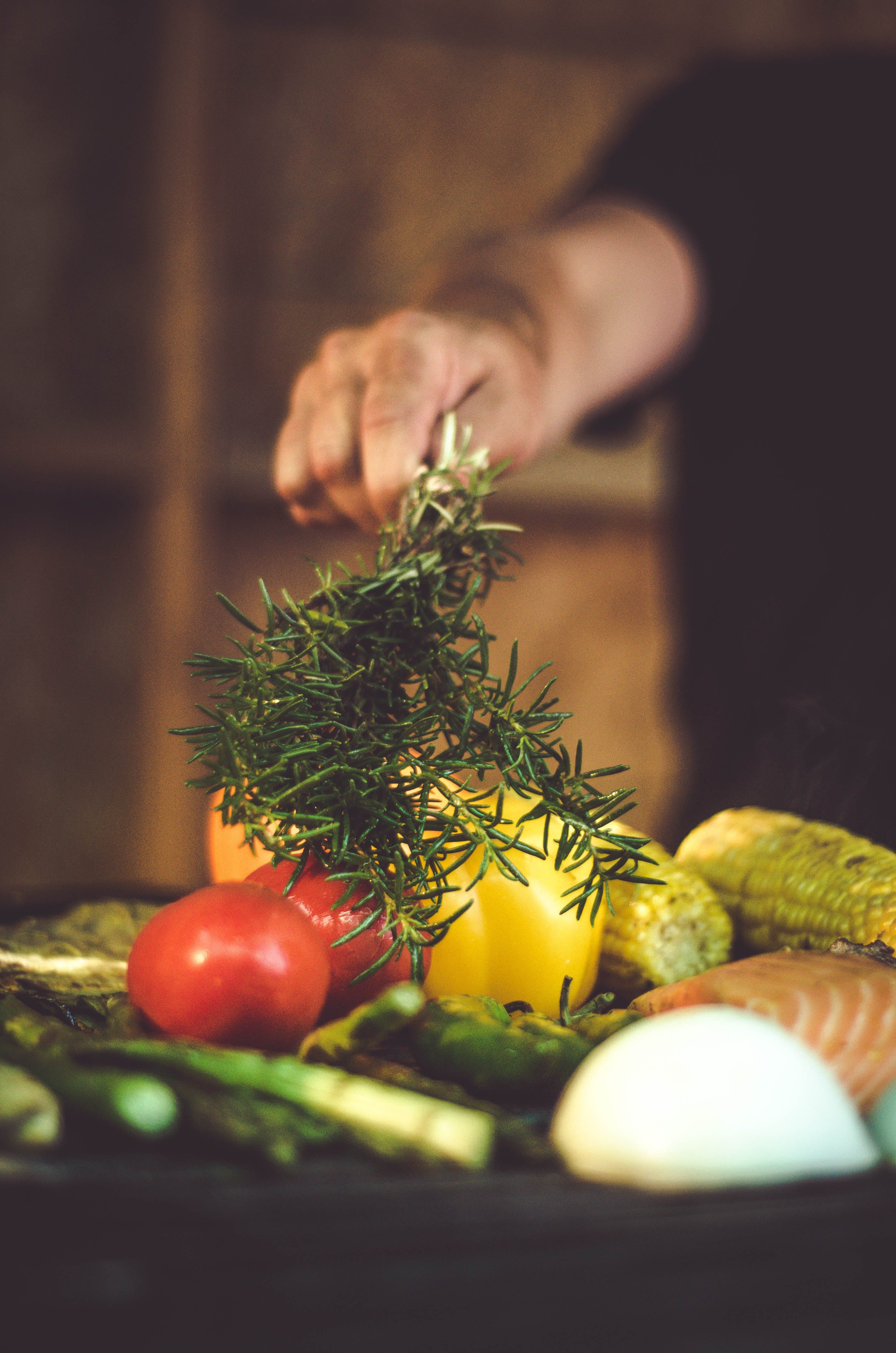 Person Putting Rosemary Into Vegetable Dish