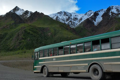 Green and White Buss on Gray Concrete Top Road Across Green Mountains Under Cloudy Sky