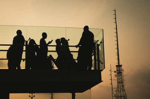 Silhouette of People Standing and Sitting on Balcony