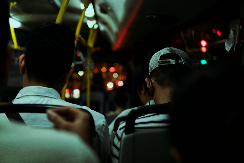 Two Men Sitting Inside Bus during Night Time
