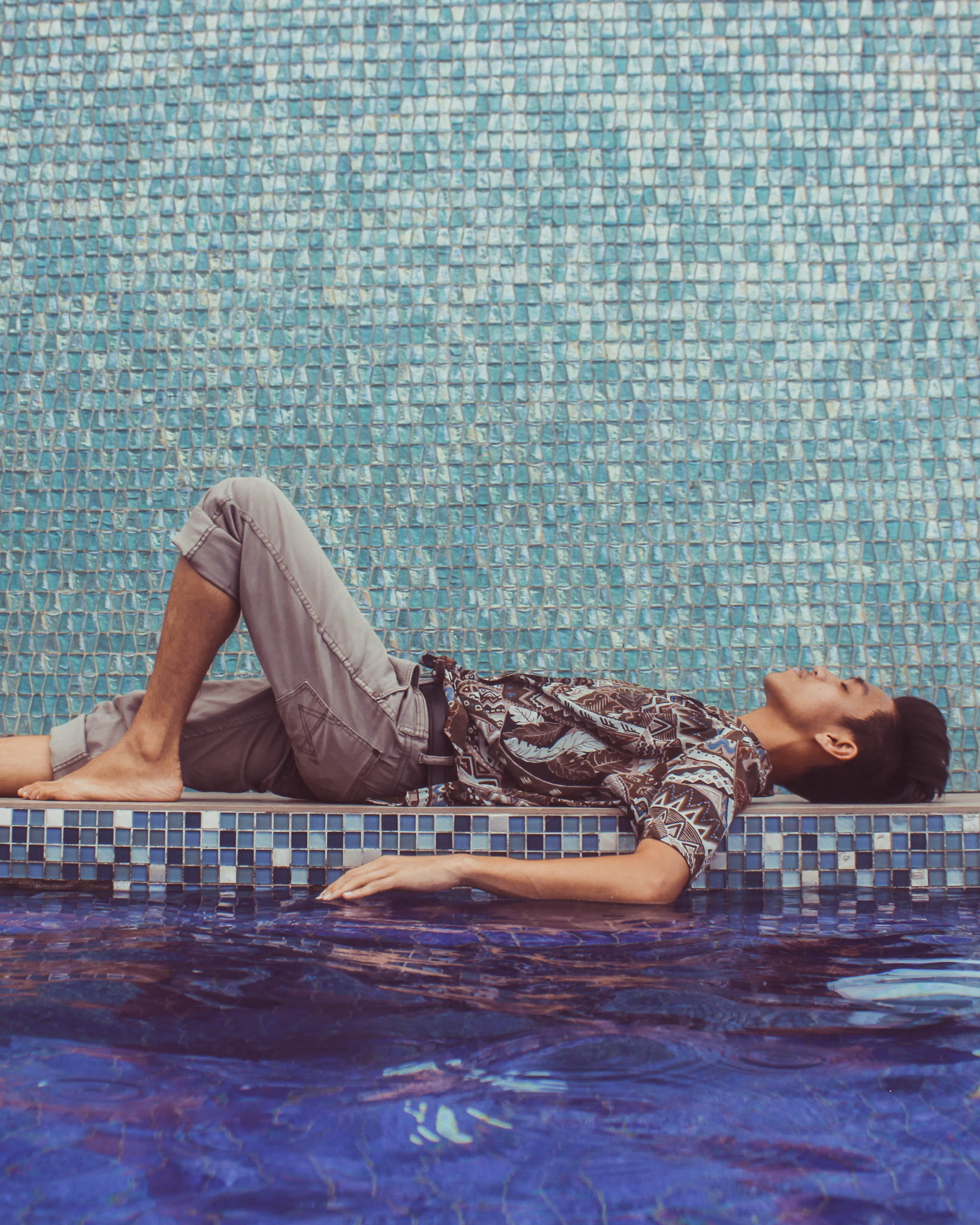 Man Lying Down on Pool Side