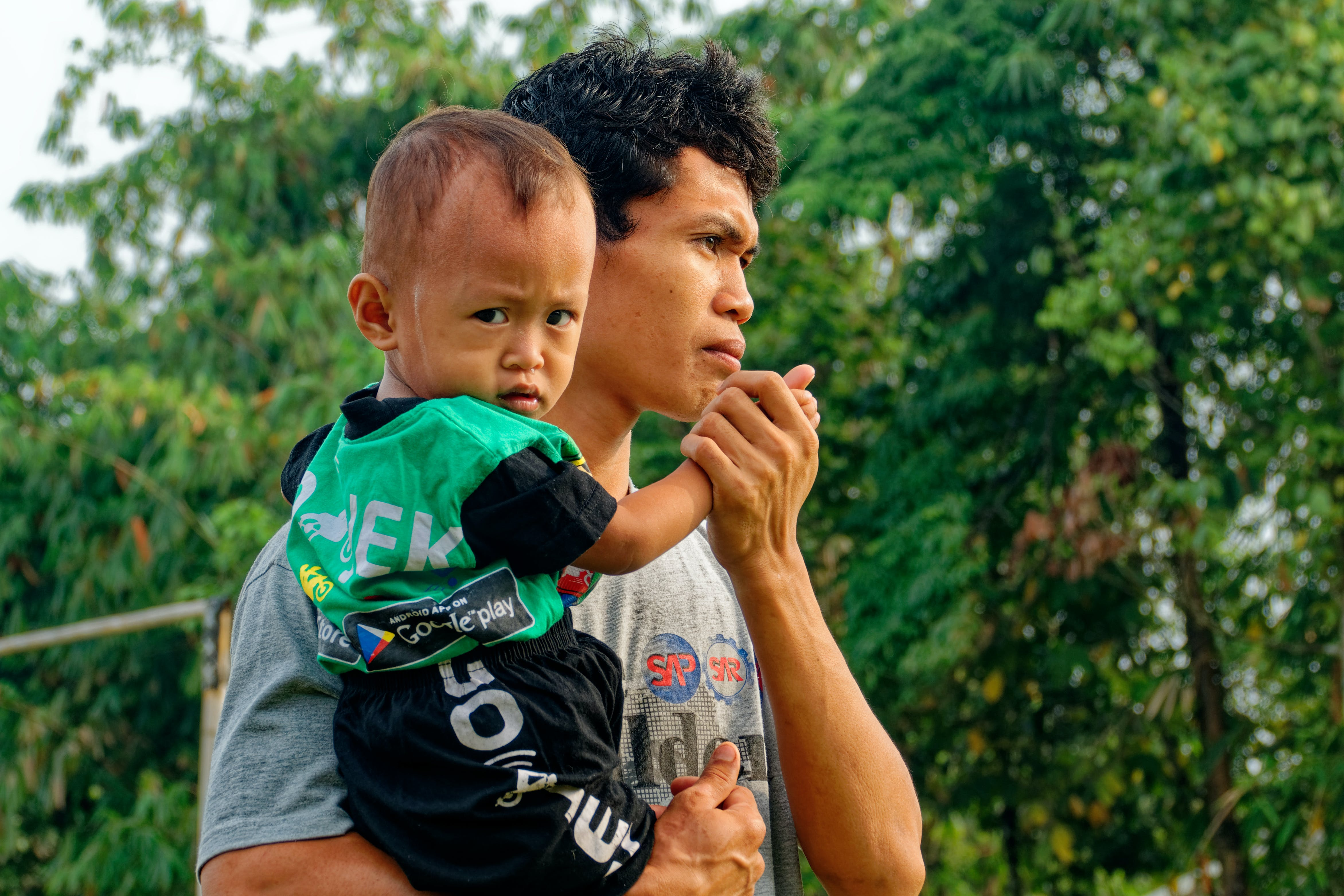 Man Carrying Baby Near Green Trees