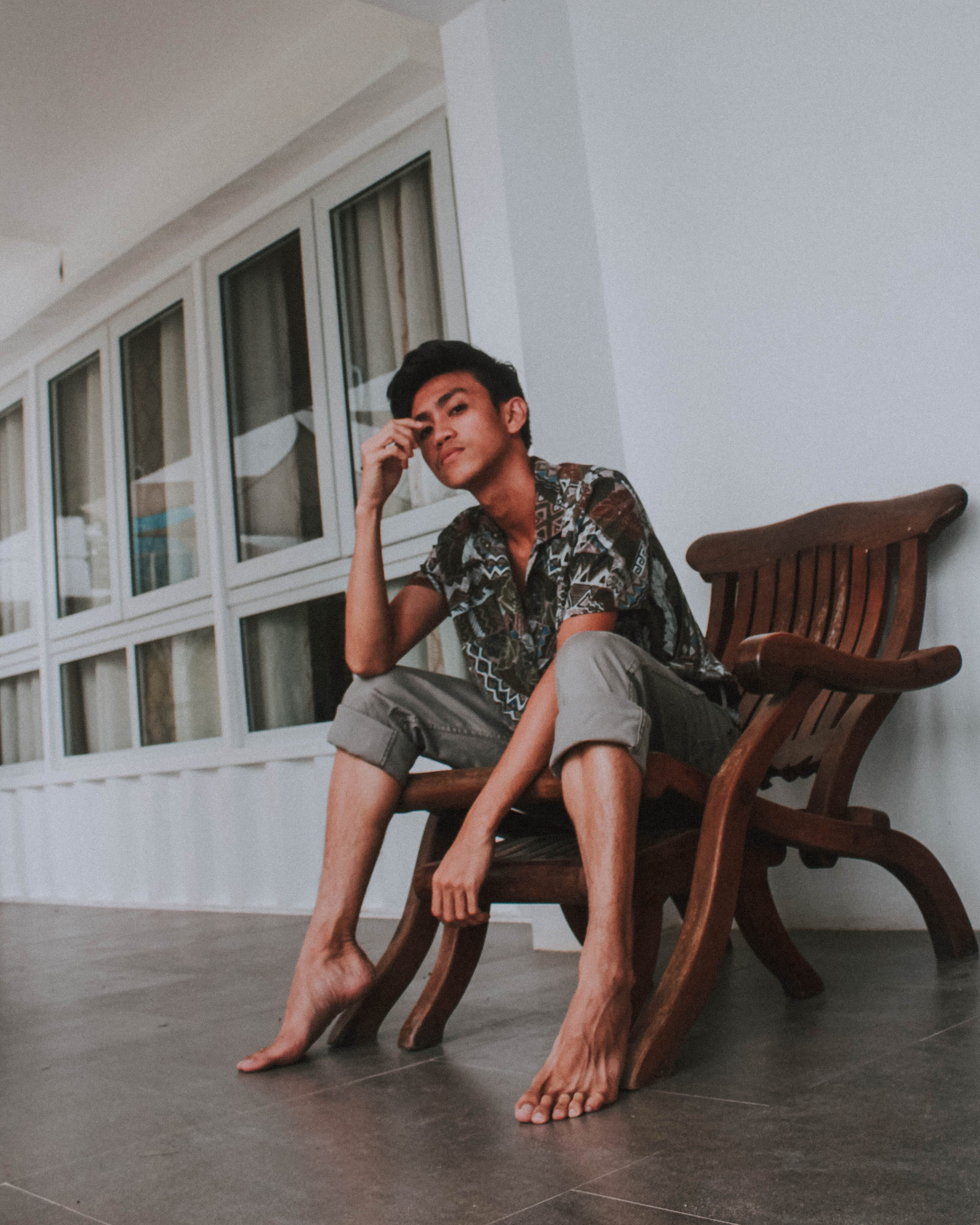 Photo of Man Sitting on Brown Wooden Armchair