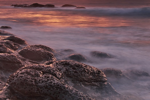 Brown and Black Rock Formations With Fog during Sunset