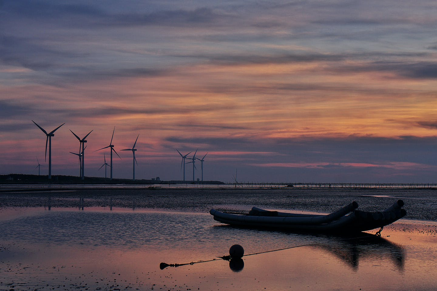 Windmills Behind Canoe Boat during Sunset