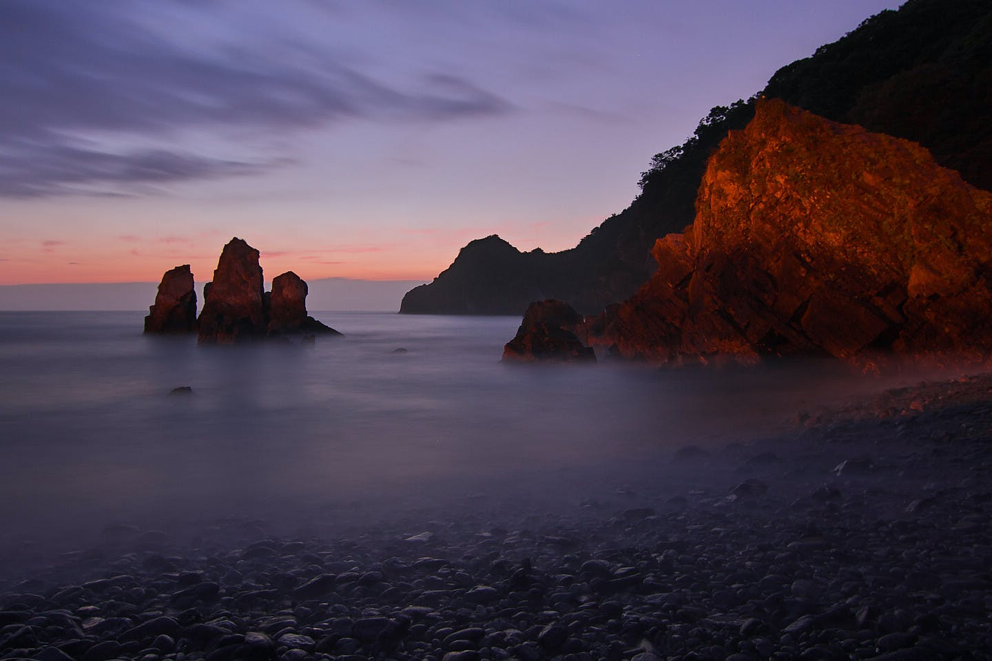 Tall Rock Formation Submerged in Water Near the Shore during Golden Hour