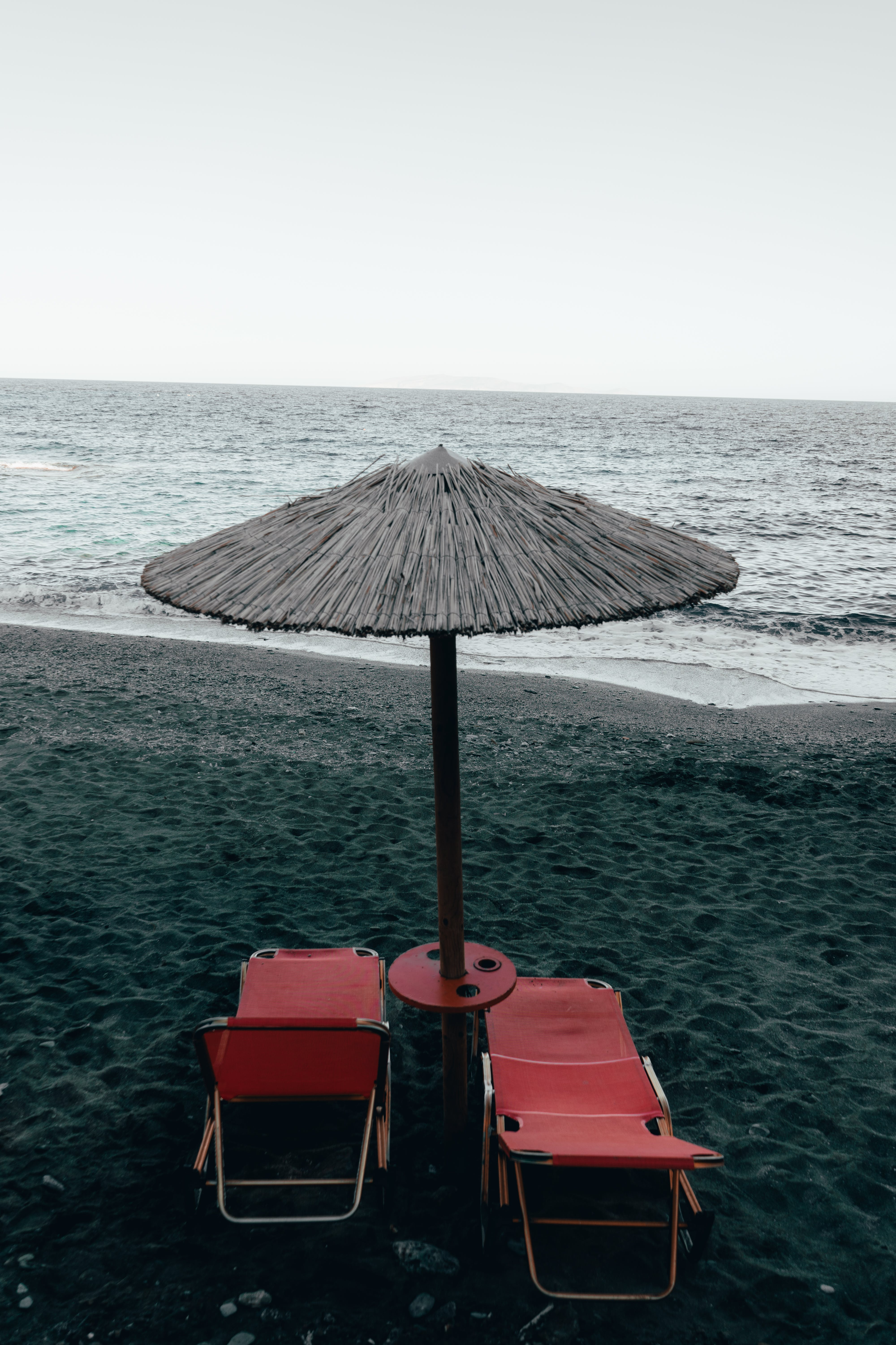 Two Red Pool Chairs Under Patio Umbrella Near Shore