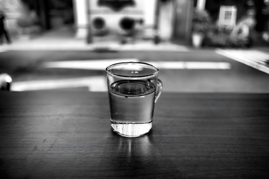 Gray Scale Photo of Glass With Water