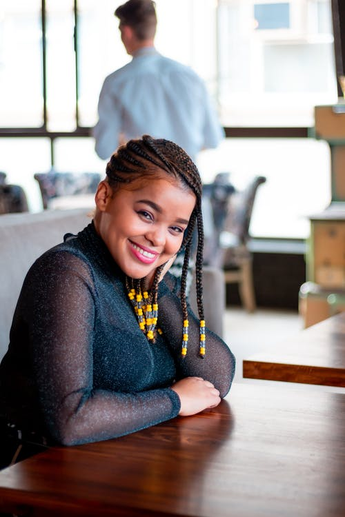 Photo of Smiling Woman With Braided Hair Sitting Near Table