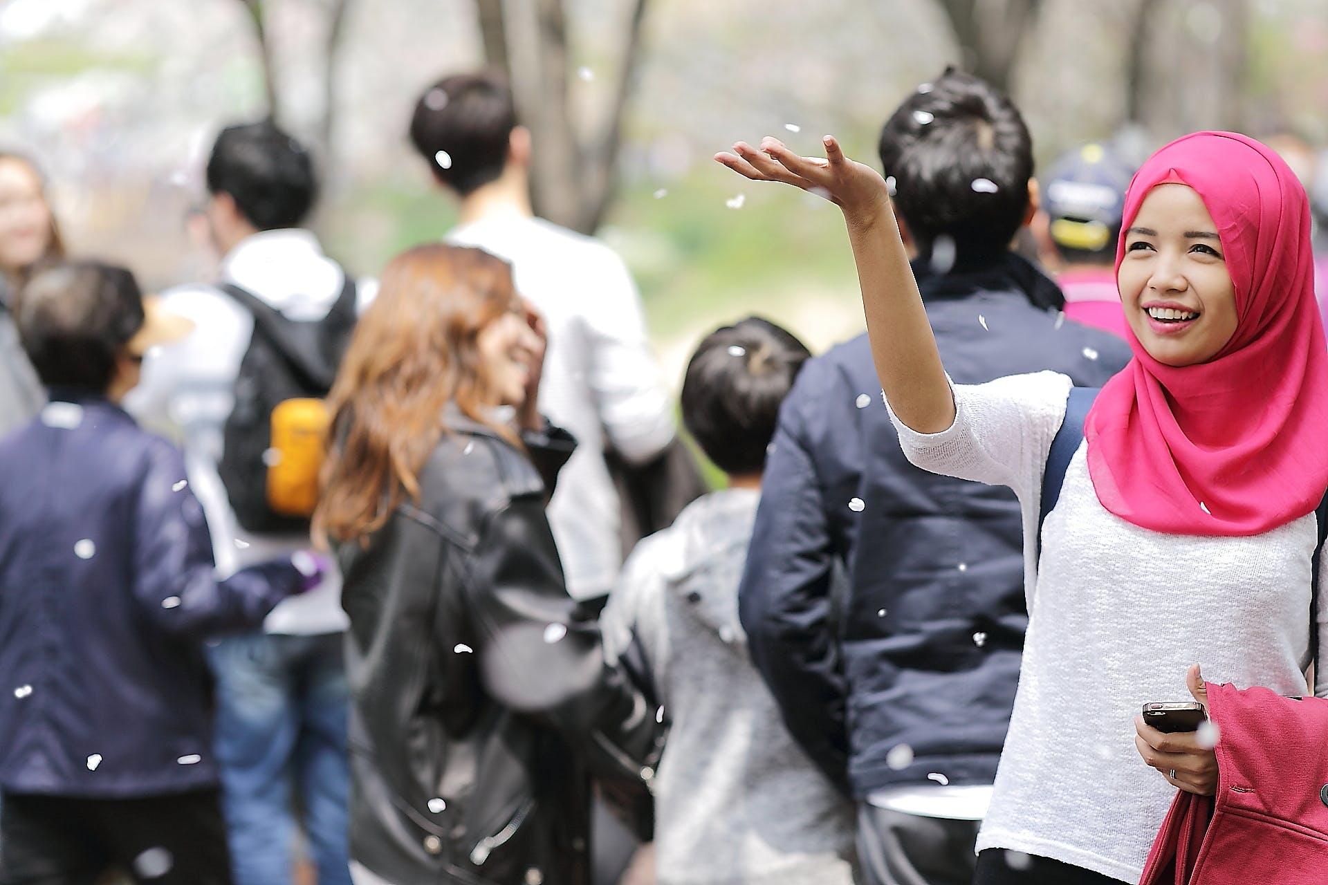 Woman Wearing Red Hijab Behind Person Wearing Black Jacket