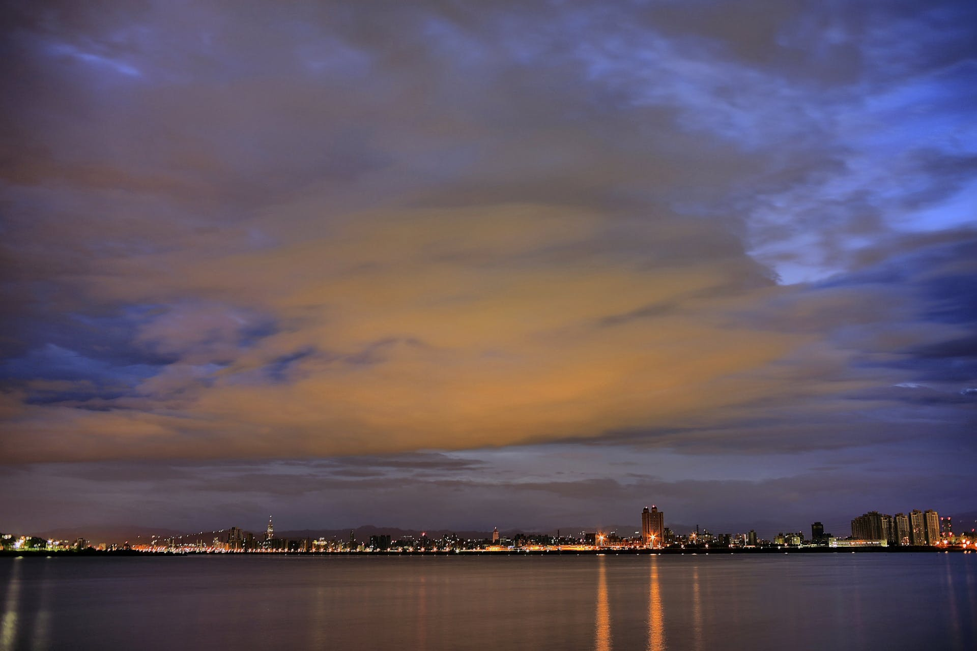 City Light Reflecting on Calm Waters Night Time