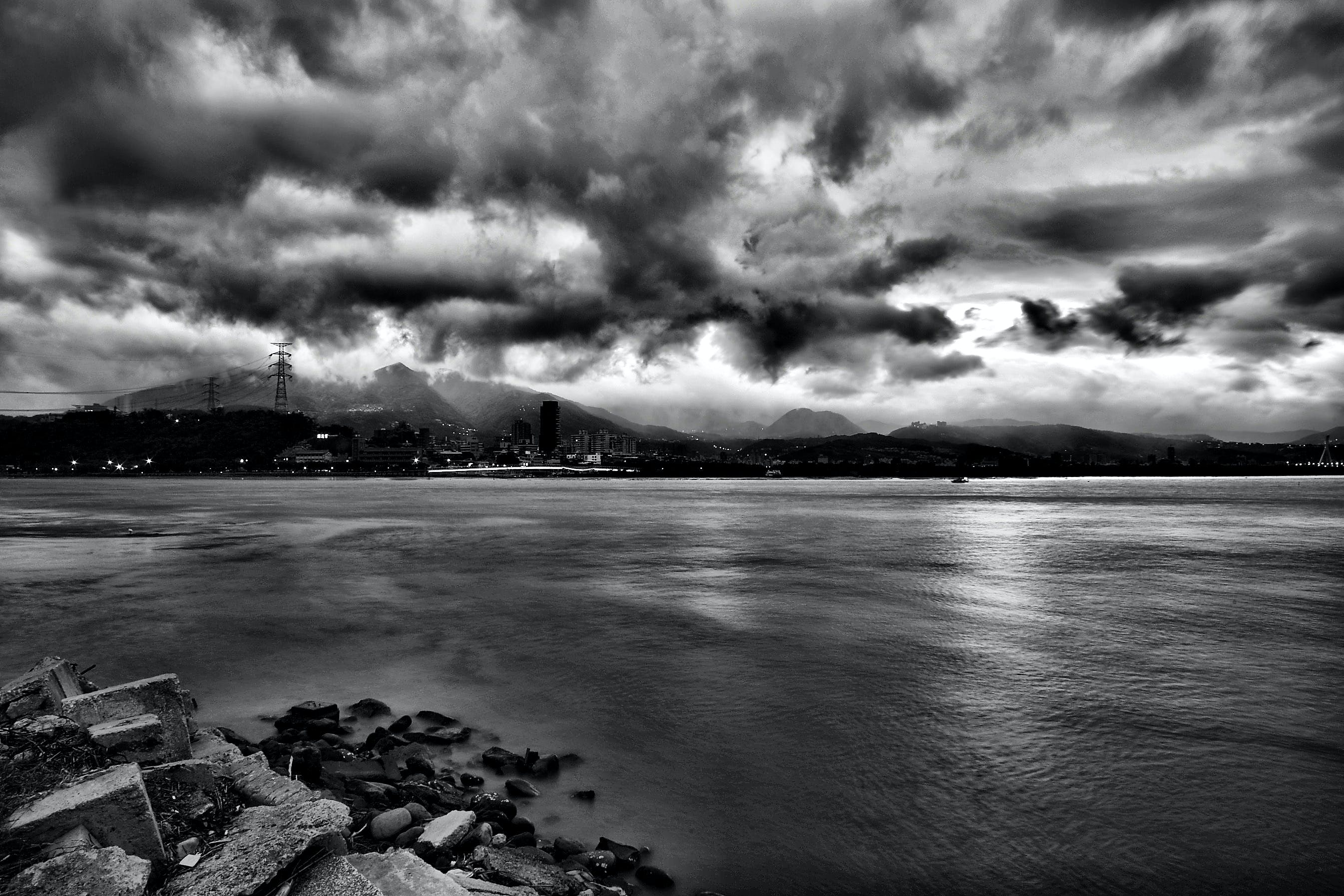 Grayscale Photo of Sea during Cloudy Sky at Daytime