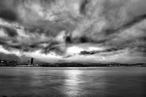 Grayscale Photo of Calm Body of Water Under Cloudy Sky