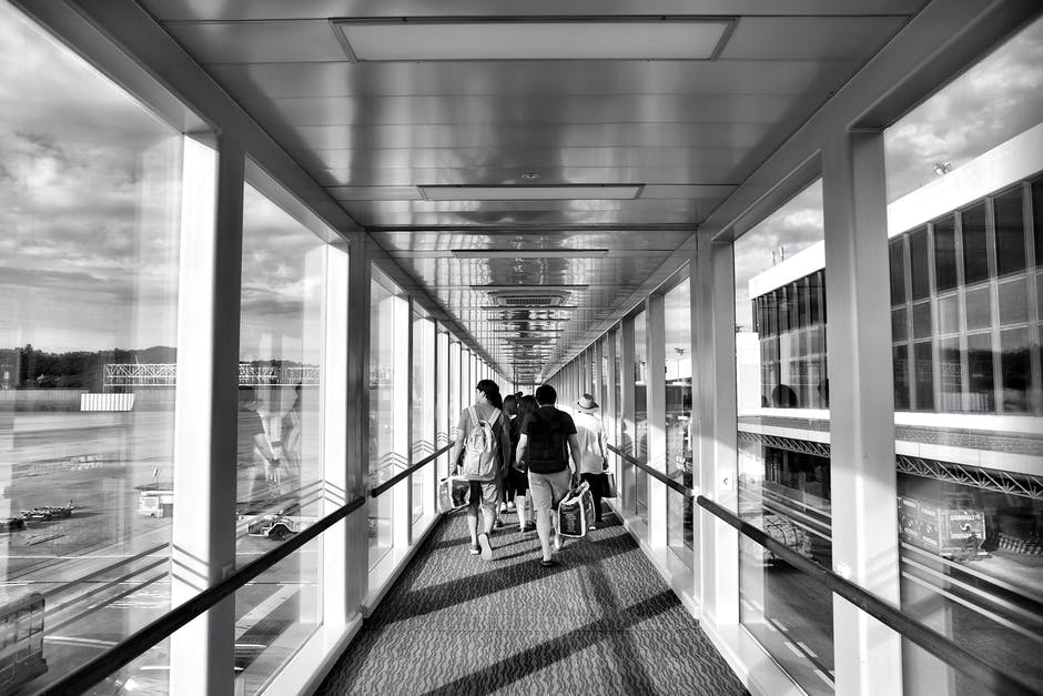 Image of travelers walking down a departures area in an airport