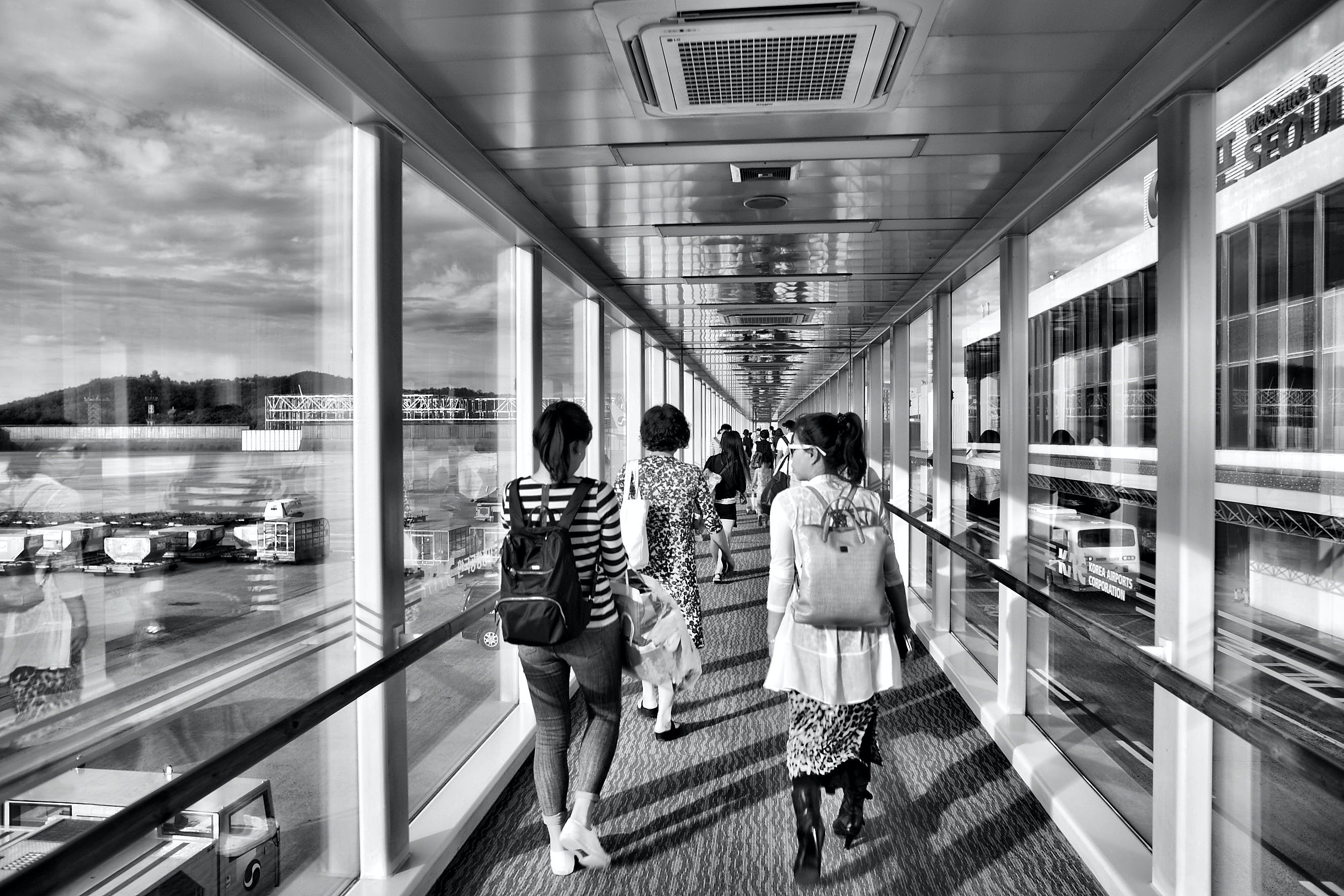Grayscale Photo of Woman Walking on Pathway