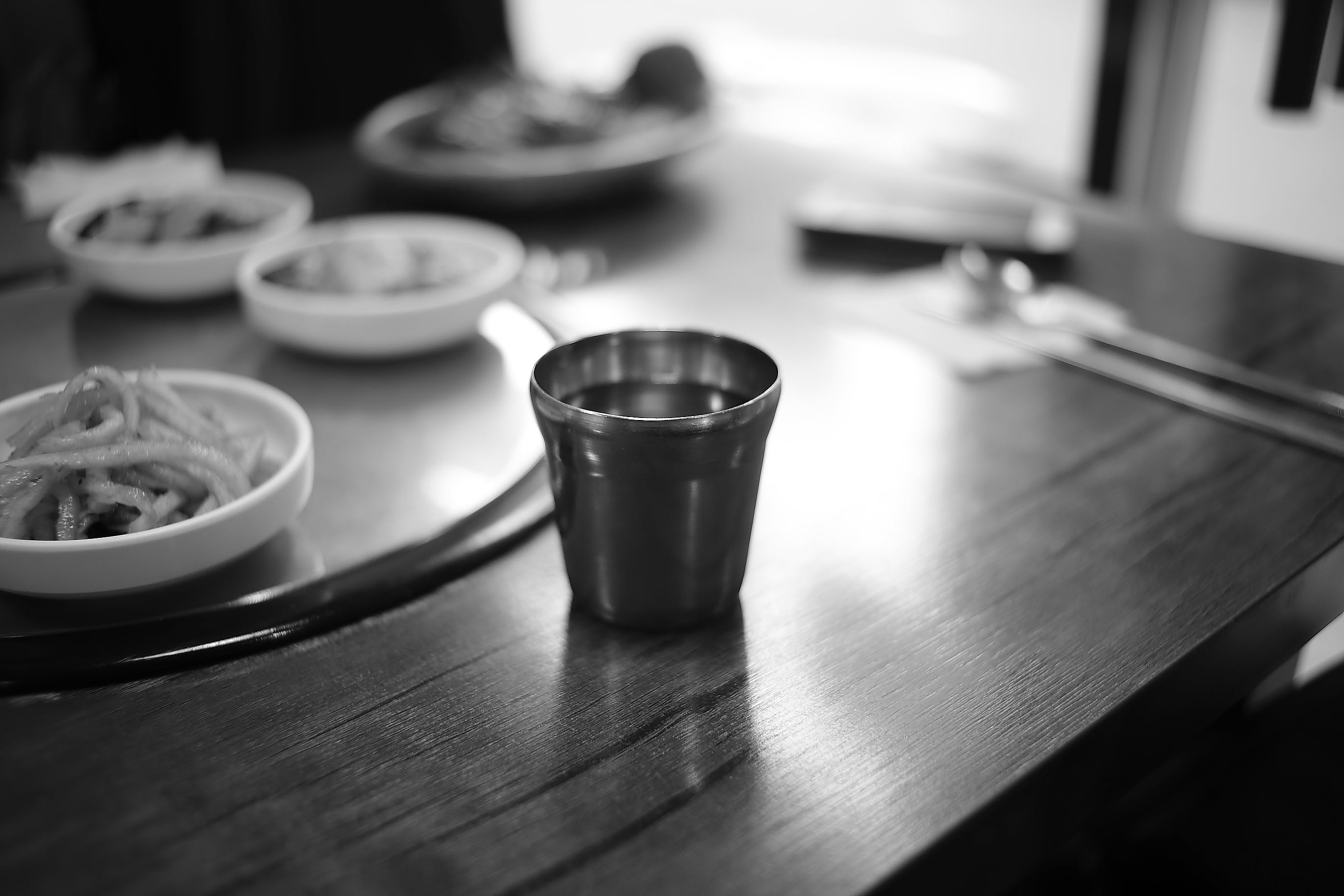 Stainless Steel Cup on Brown Wooden Top Table