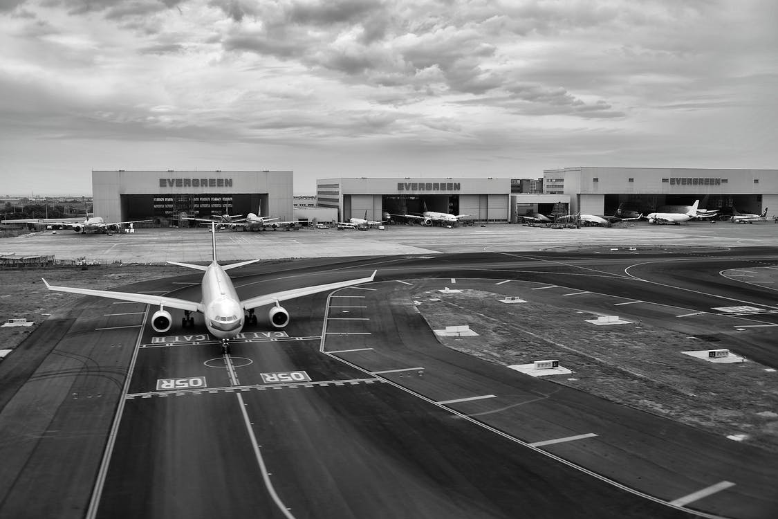 Gray Scale of Air Plane on Runway Under Cloudy Day