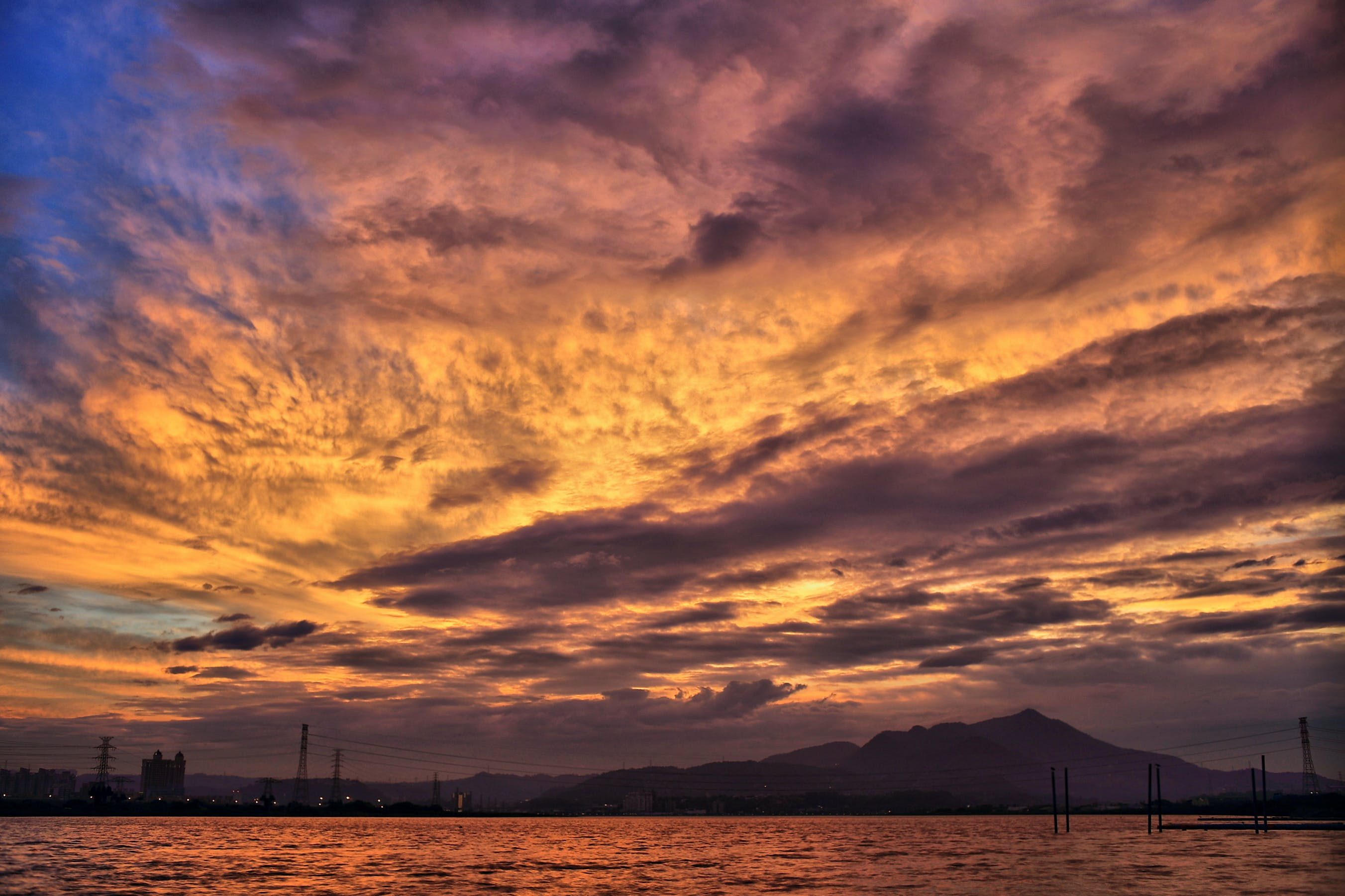 Sea and Silhouette of Mountain Under Orange Sky during Golden Hour