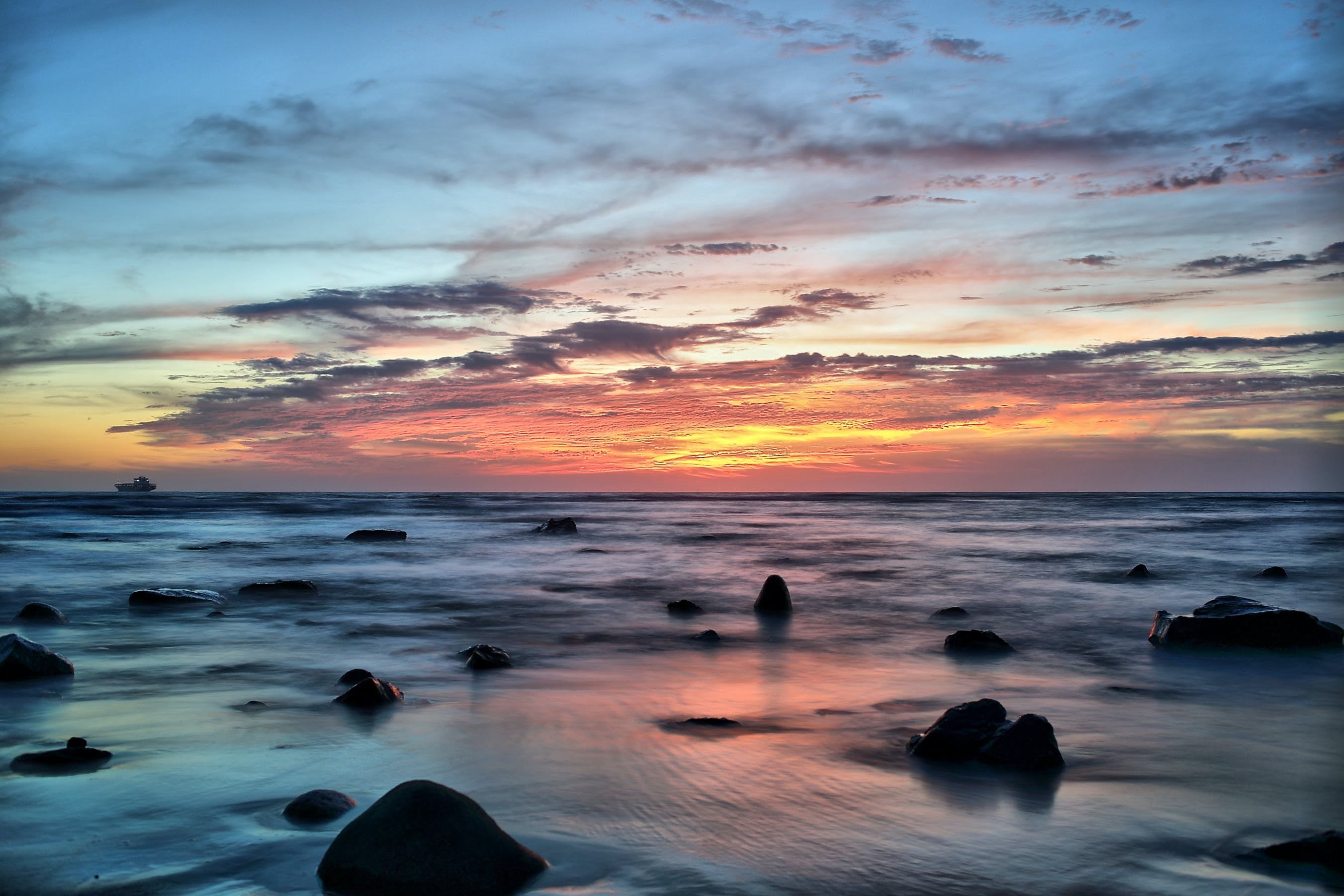 Silhouette of Stones on Seawater during Sunset