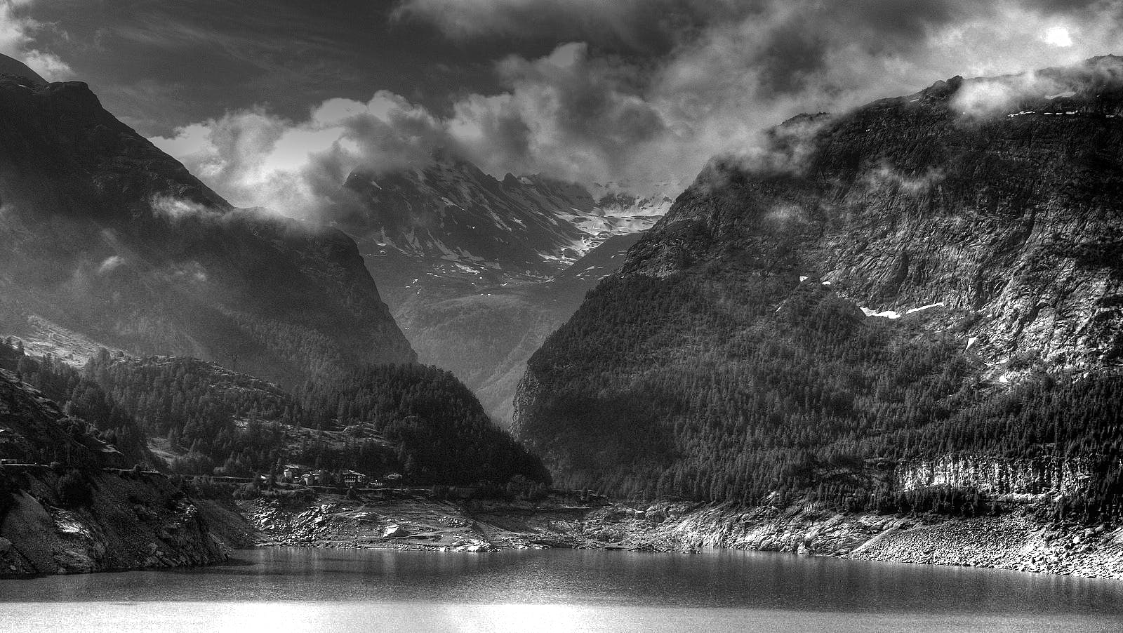 Grey Scale Photo of Body of Water Near Mountain Ranges
