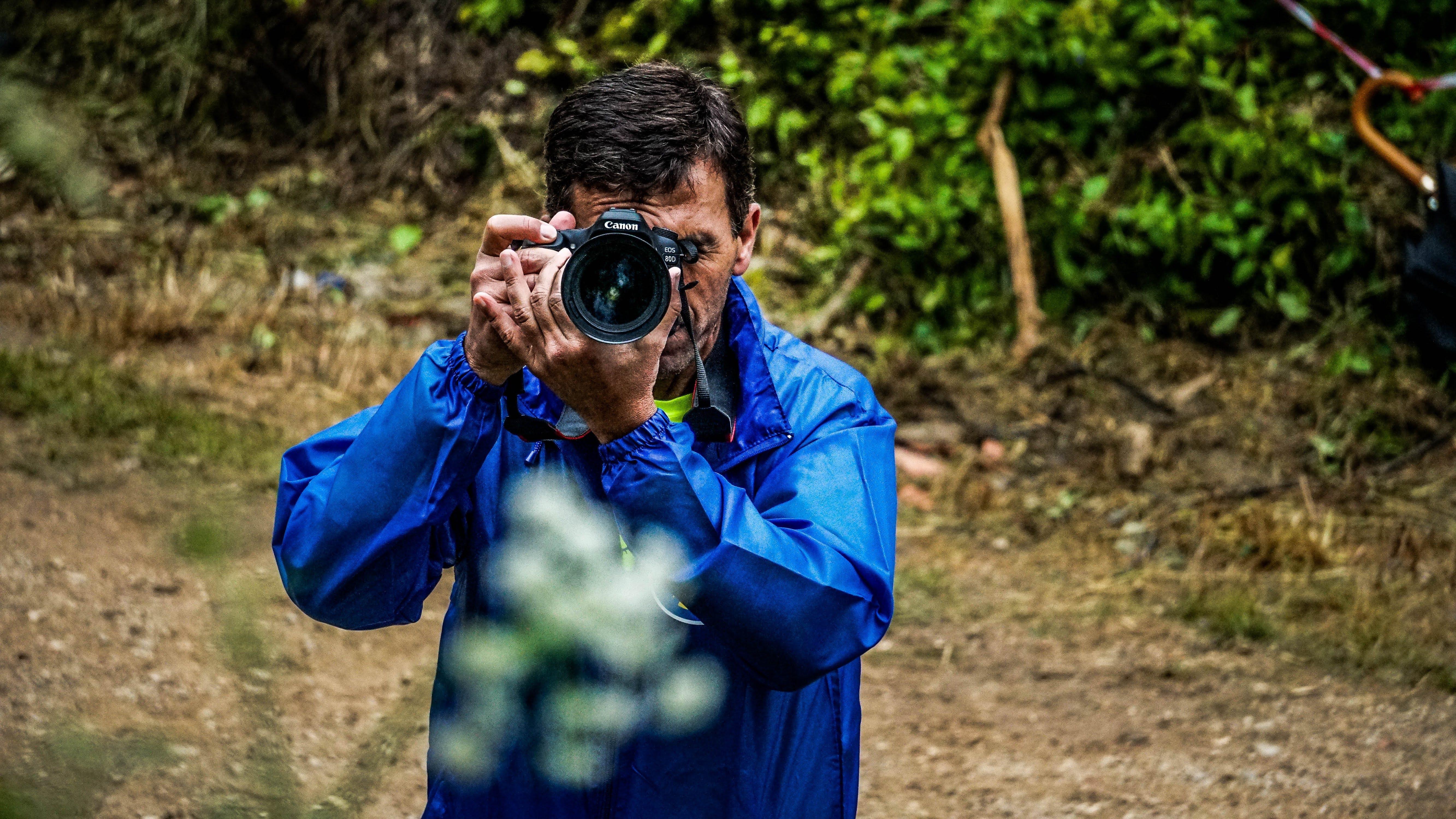 Man Taking Photo Near Woods