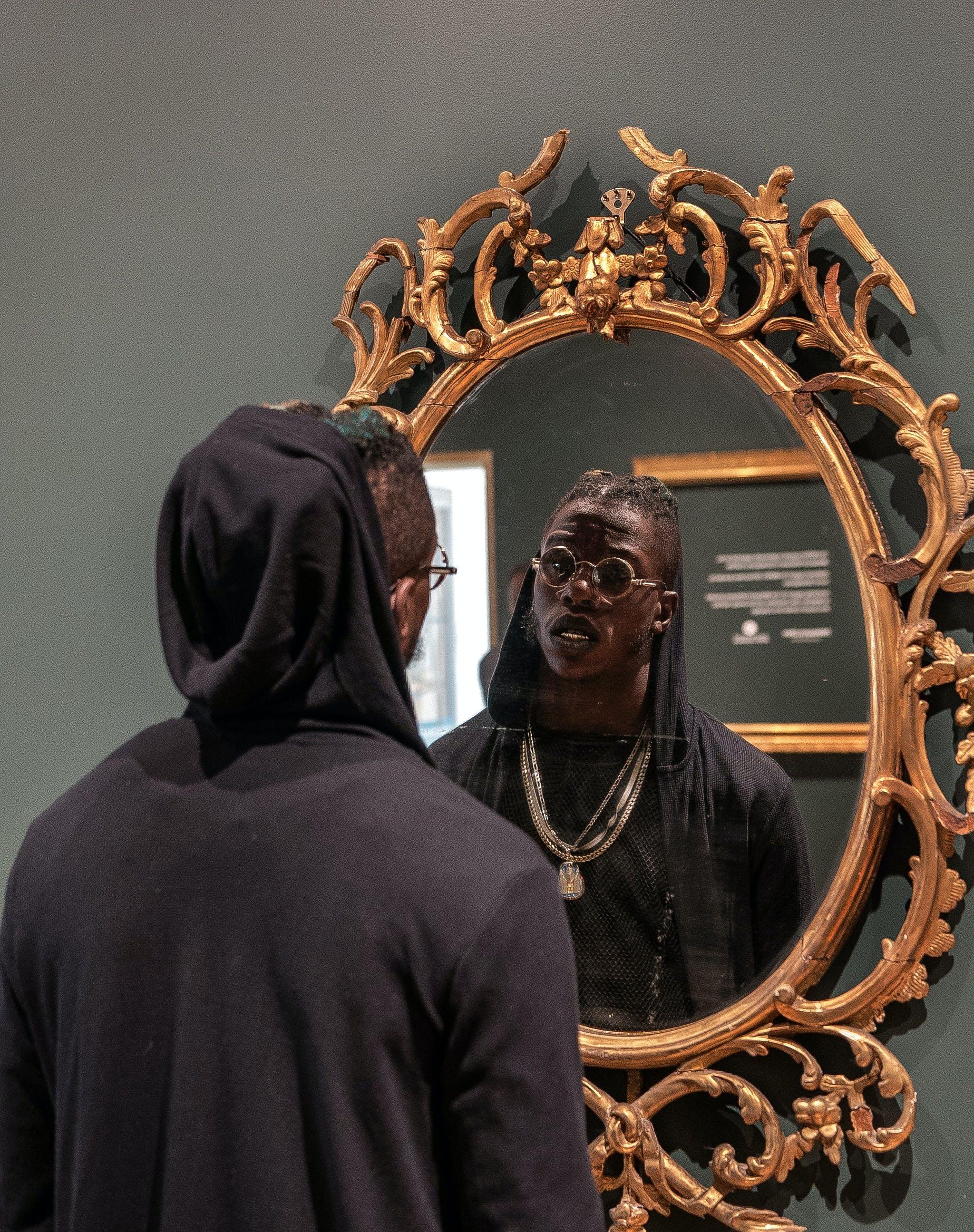 Man Facing Brown Framed Mirror