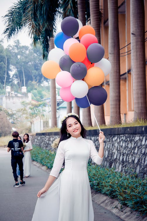 Woman Wearing White Dress While Holding Bundle of Balloons