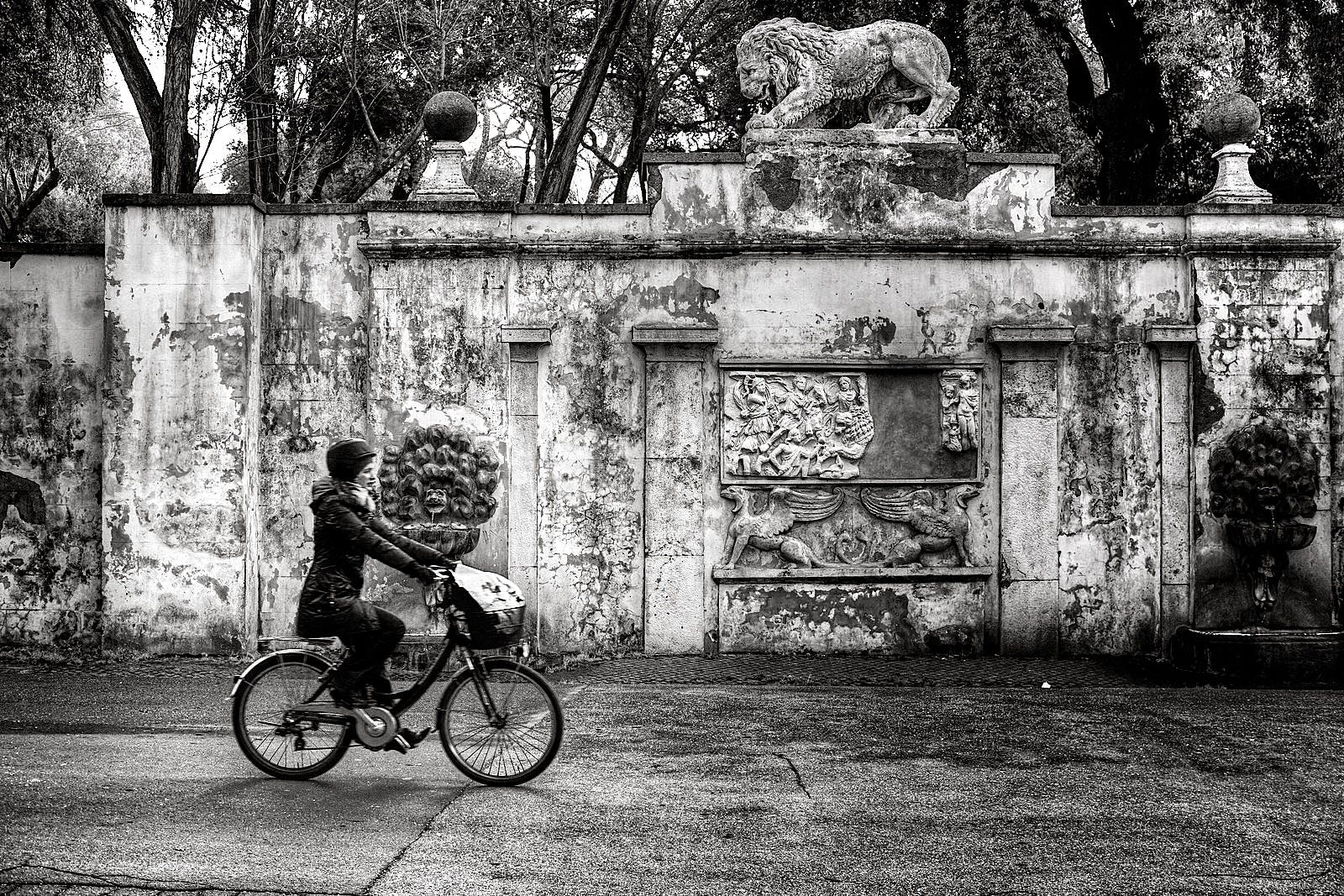 Woman Wearing Jacket and Pants Riding on Bicycle Near Concrete Wall Greyscale Photo