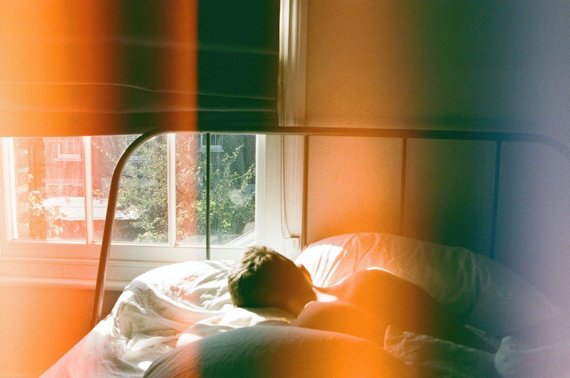 Person Lying in Bed Beside Window