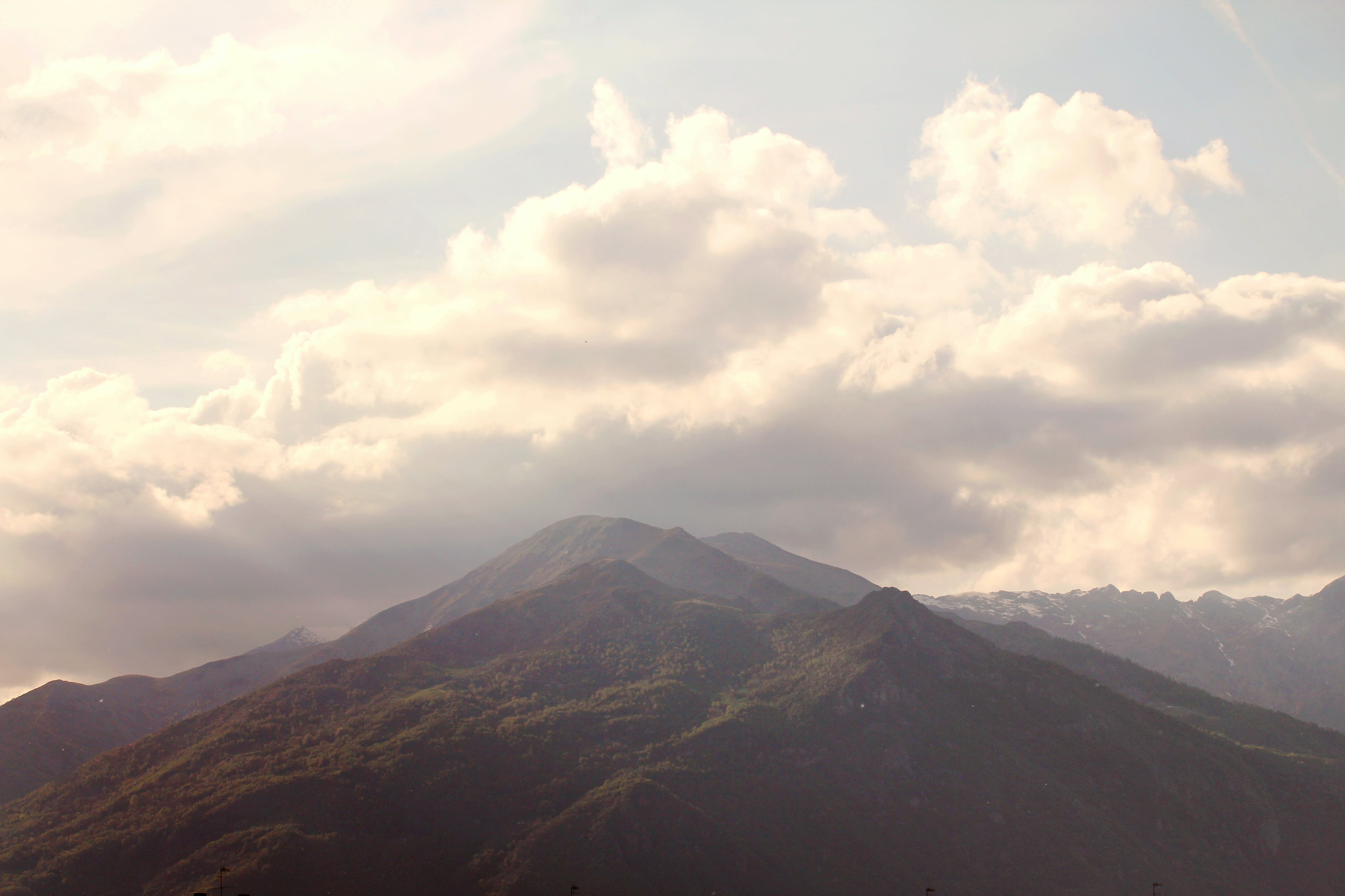 Green and Brown Mountain Peak With White Clouds