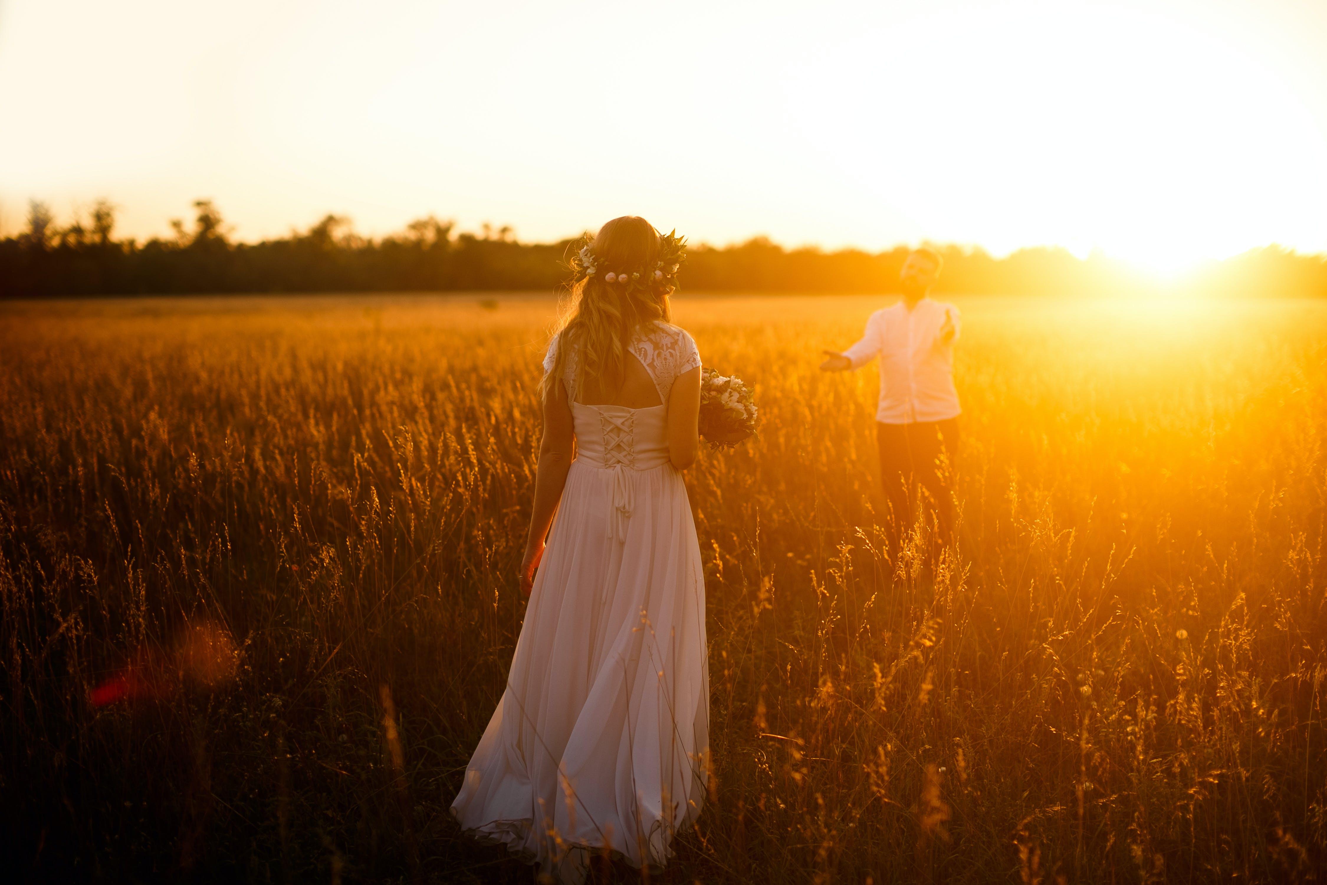 Woman In White Dress Holding Bouquet on Field