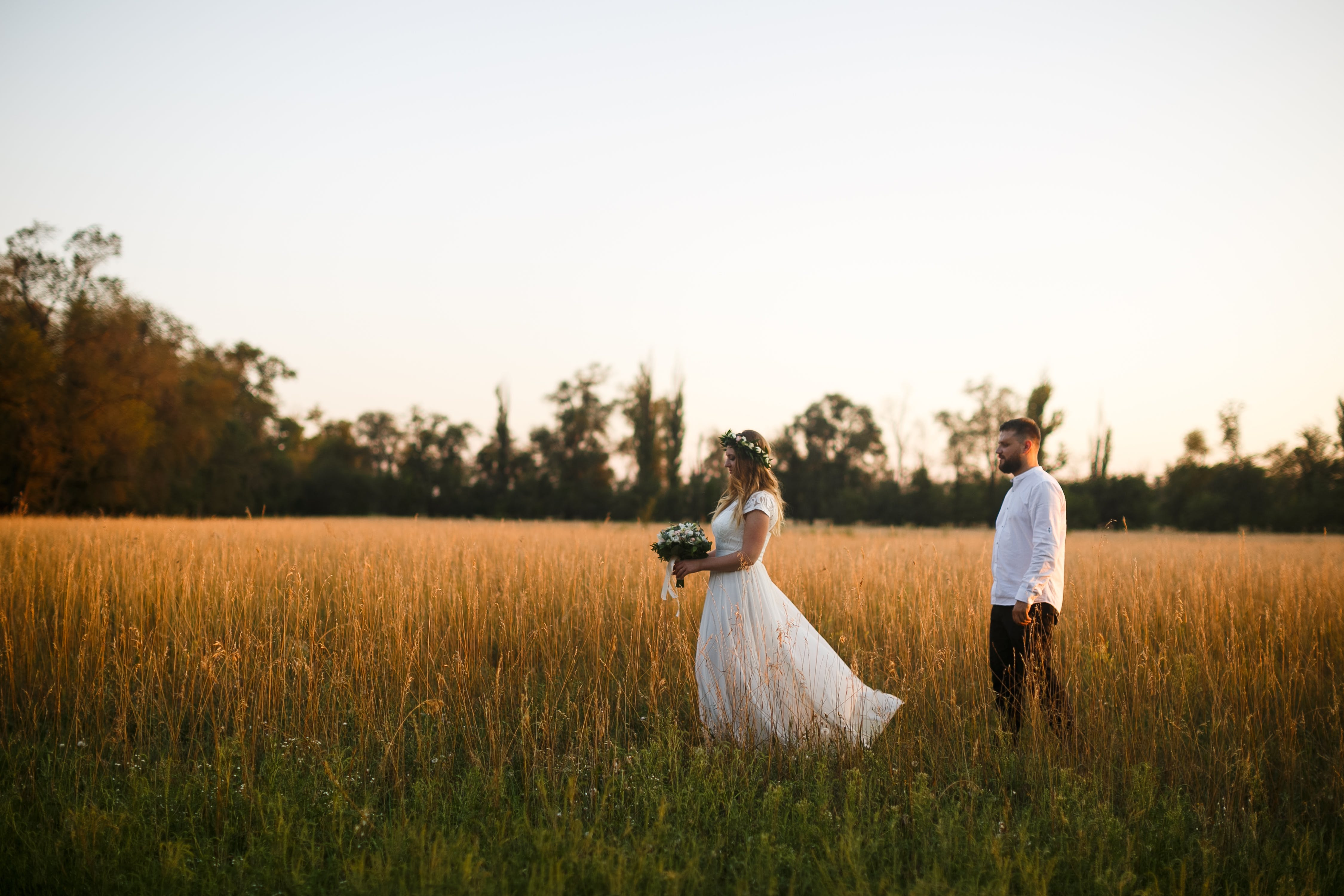 Groom Standing Next to Bride Holding Bouquet of Flower on Grass Field