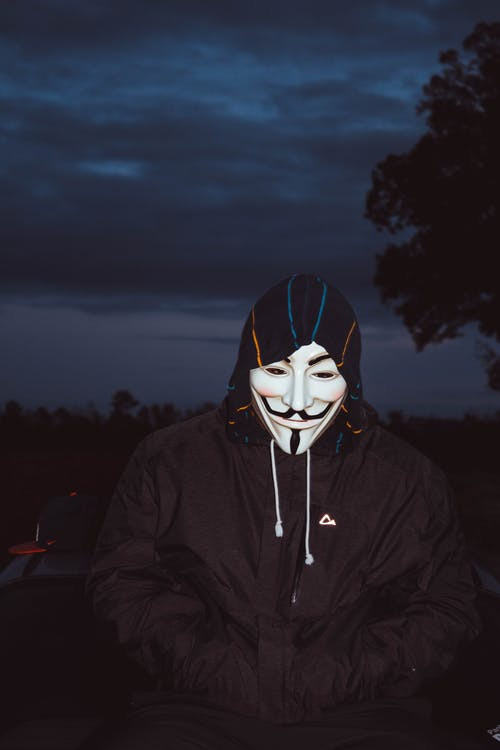Person Wearing Guy Fawkes Mask and Black Jacket